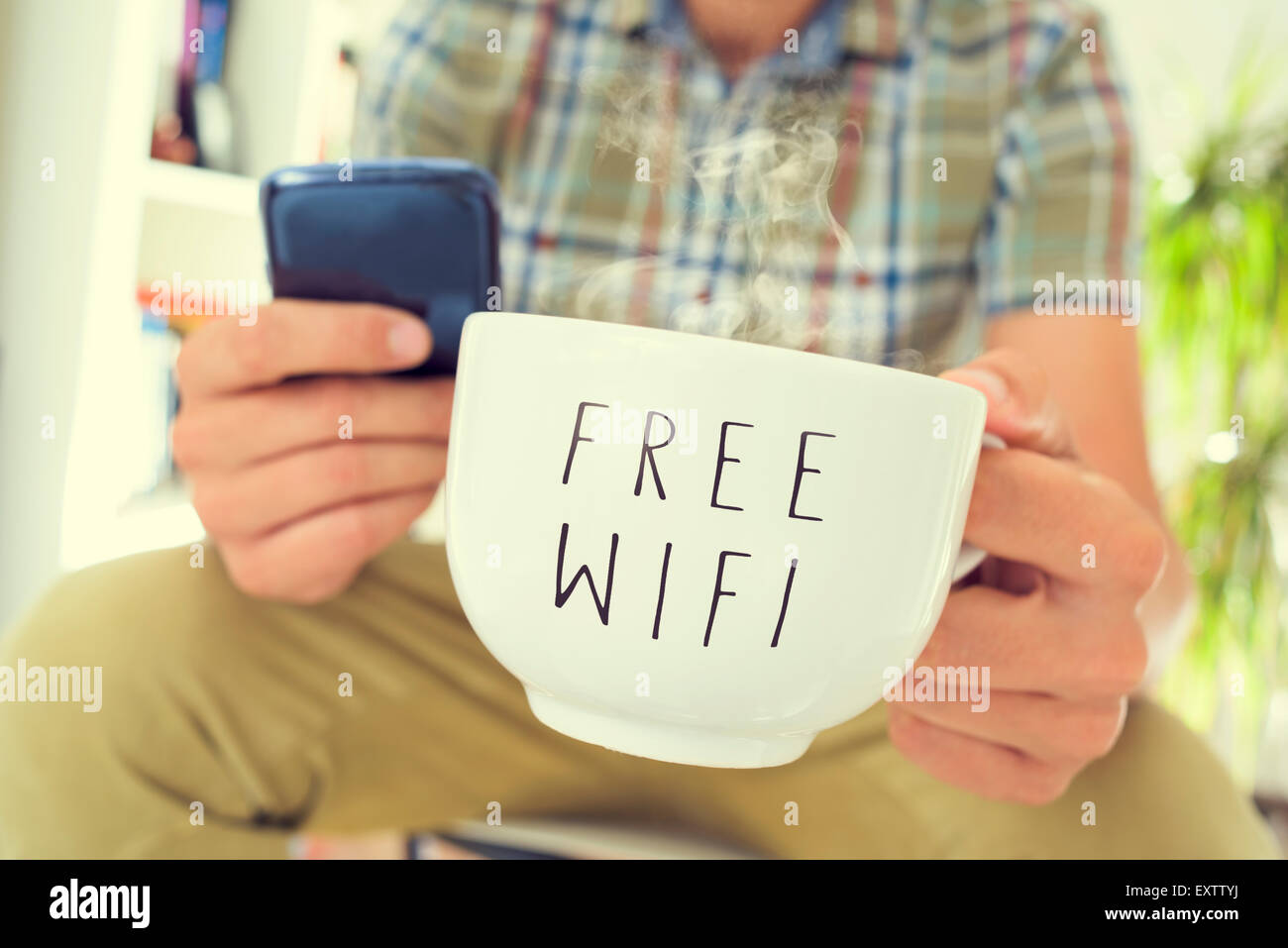 Gros plan du jeune homme de race blanche à l'aide d'un smartphone avec une tasse de café ou de Photo Stock