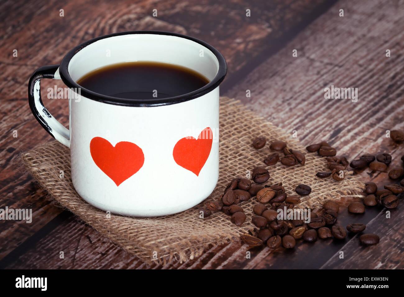 Une tasse de café noir dans un vieux mug émaillé avec des cœurs, les grains de café sur fond rustique vintage Banque D'Images