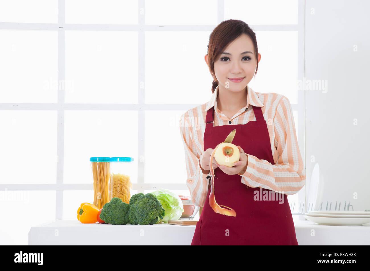 Young woman peeling une pomme et souriant à la caméra, Photo Stock