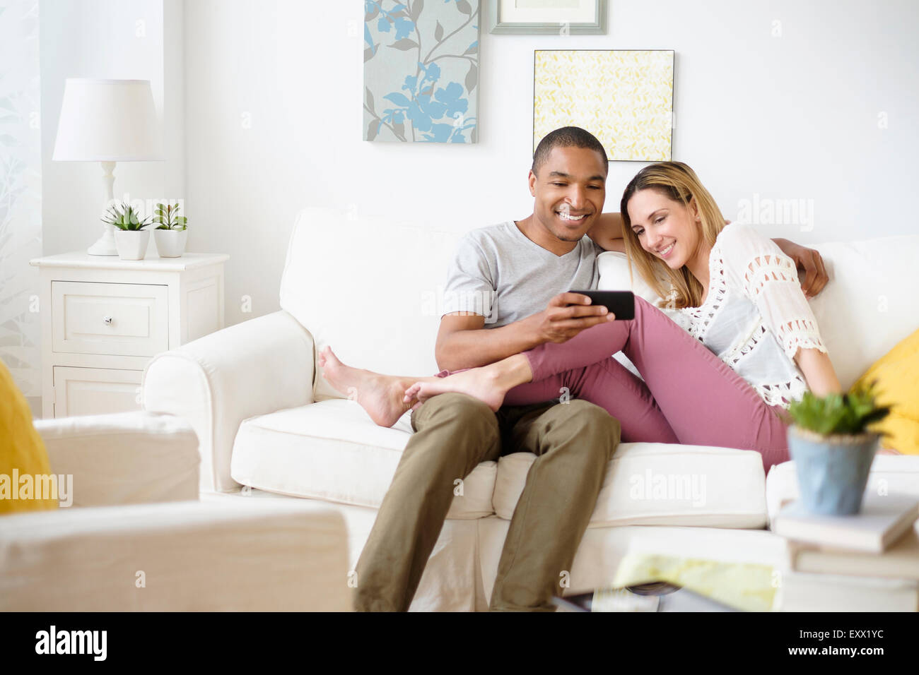 Mid adult couple looking at smart phone in living room Photo Stock