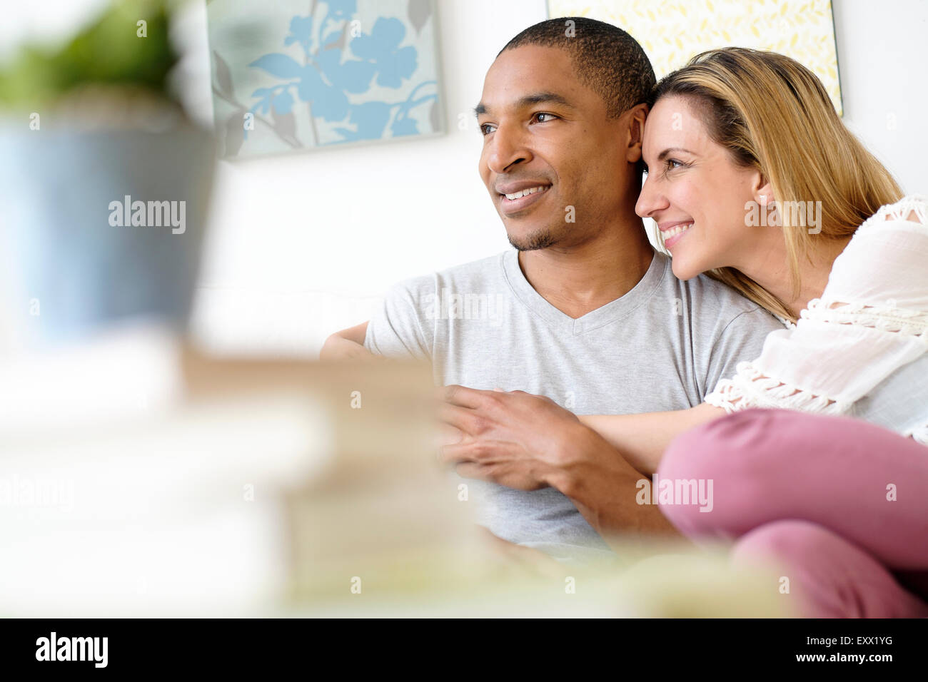 Young couple embracing in living room Photo Stock
