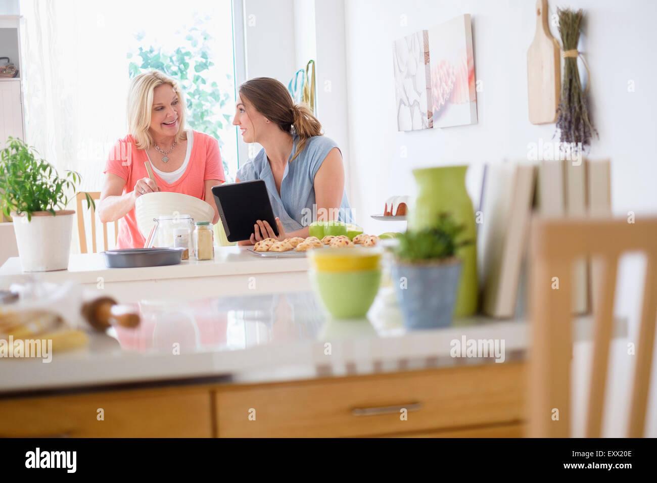 Mère avec sa fille adulte baking in kitchen Photo Stock