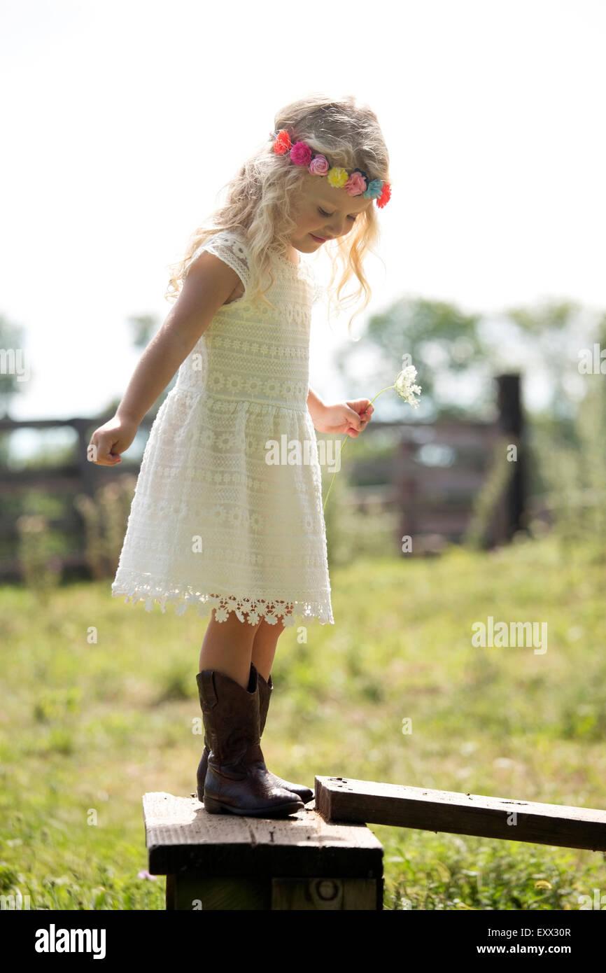 Cute girl (4-5) in white dress debout sur une clôture en prairie Banque D'Images