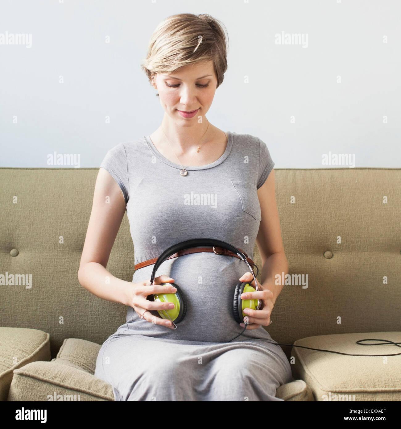 Pregnant woman holding casque sur l'abdomen Photo Stock