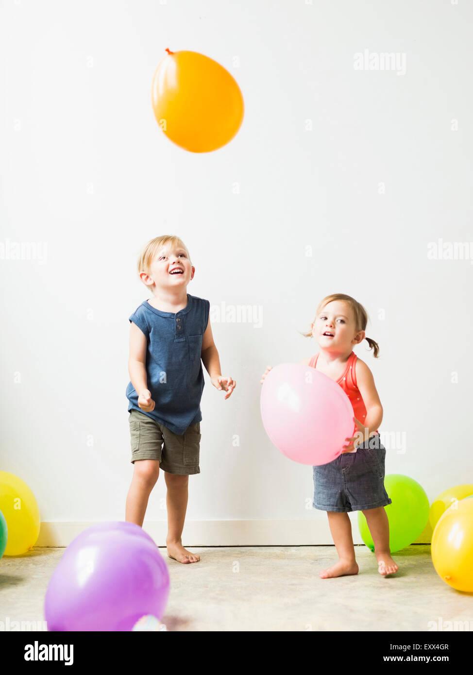 Enfants (2-3) en jouant avec des ballons Banque D'Images