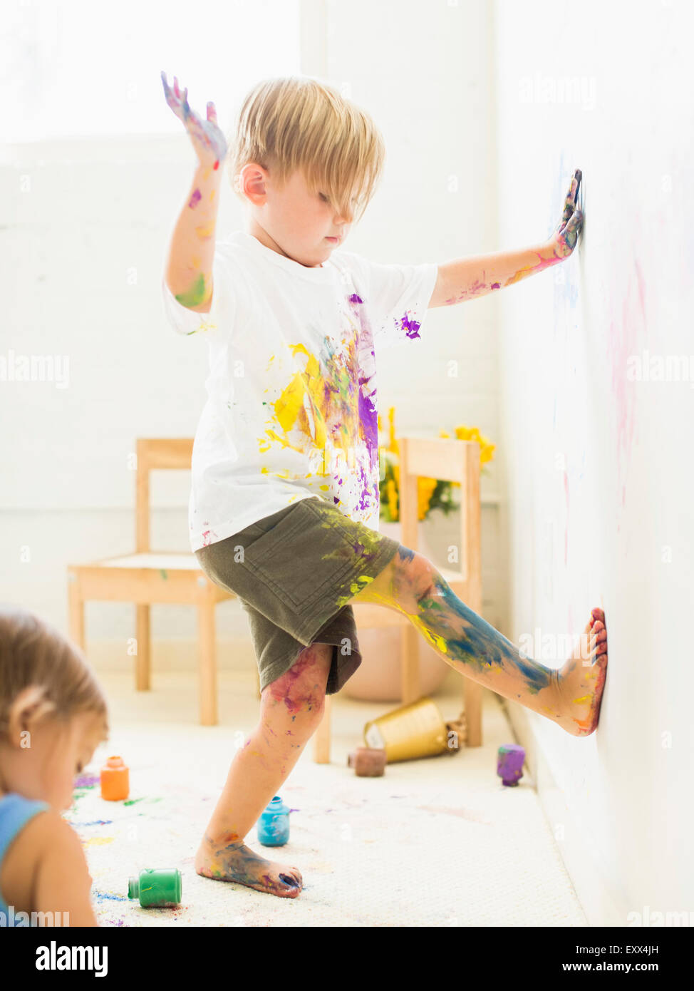 Boy (2-3) peinture sur le mur avec les mains et les jambes Photo Stock
