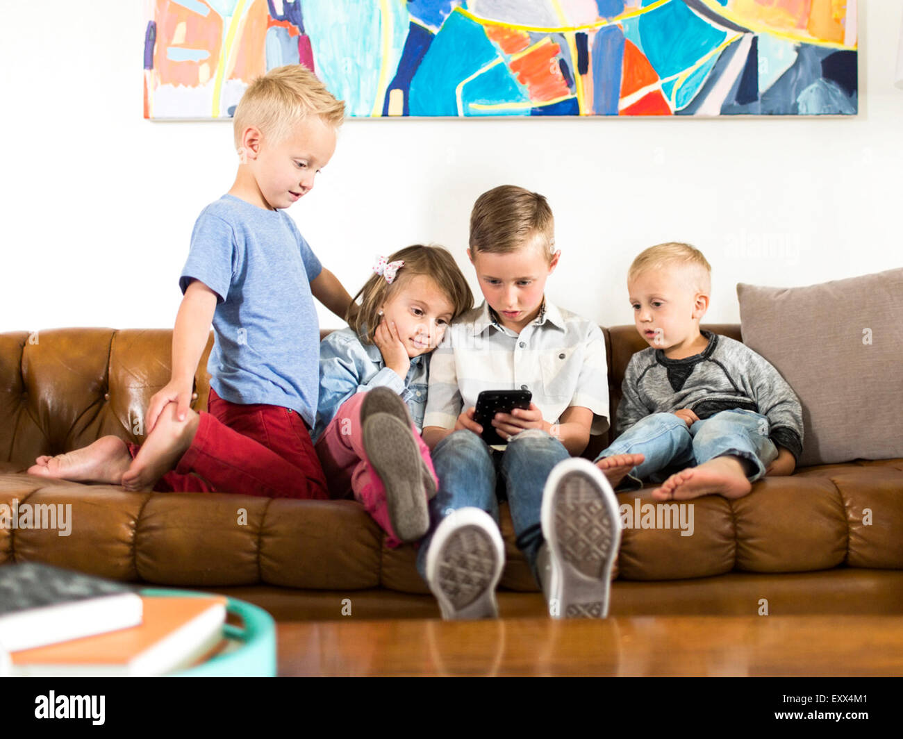 Enfants (2-3, 4-5, 6-7) sitting on sofa et using smartphone Photo Stock