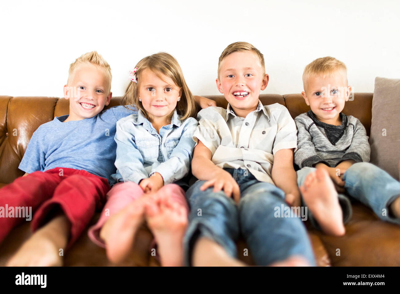 Smiling Children (2-3, 4-5, 6-7) sitting on sofa Photo Stock