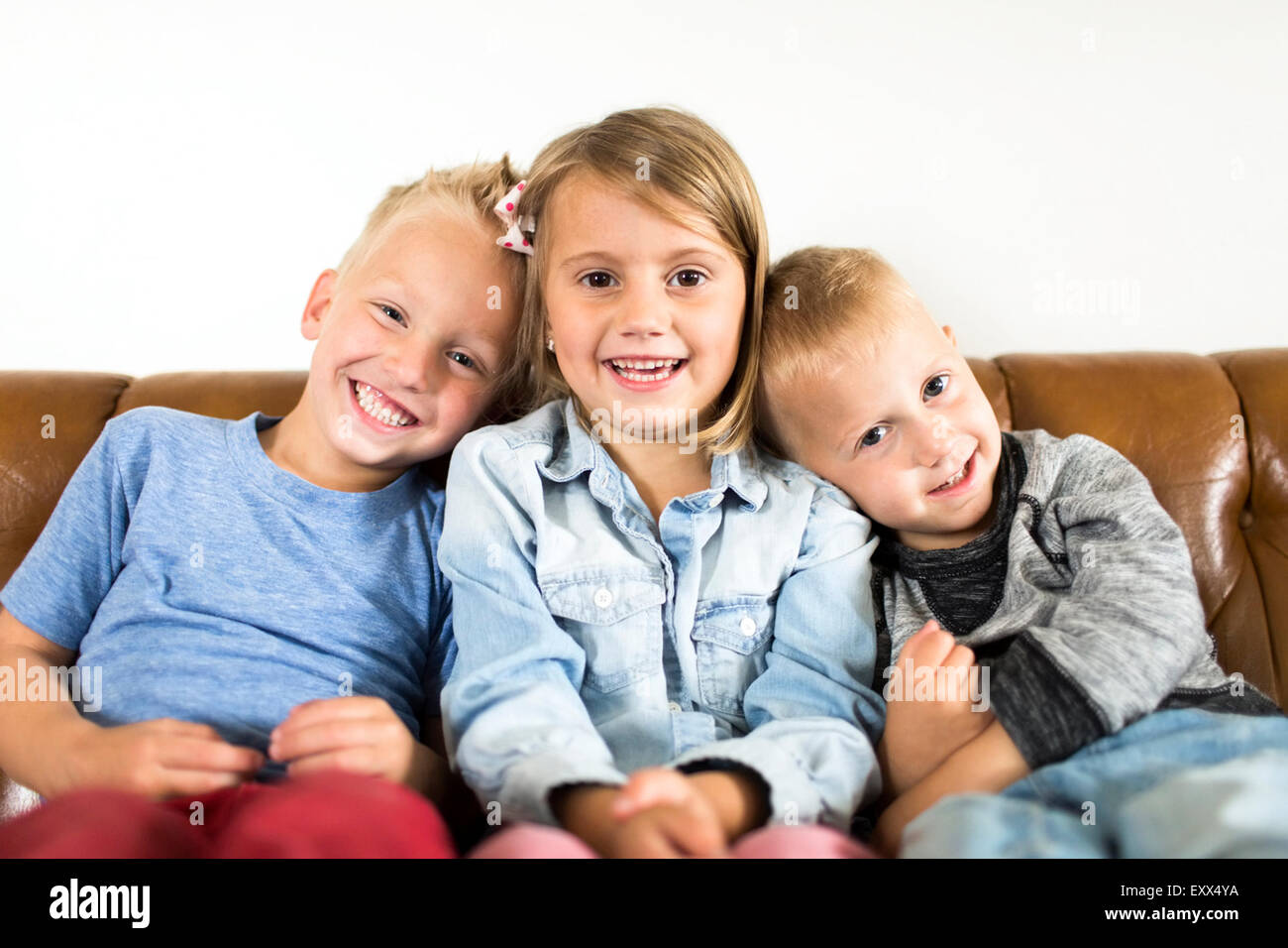 Smiling Children (2-3, 4-5) sitting on sofa Photo Stock