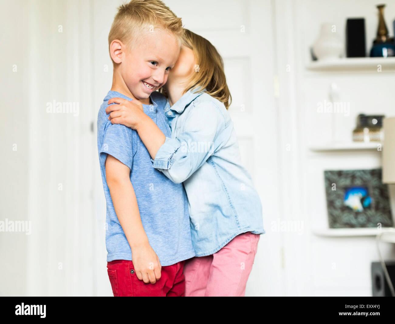 Little girl (4-5) du frère chuchotant à l'oreille (4-5) Photo Stock