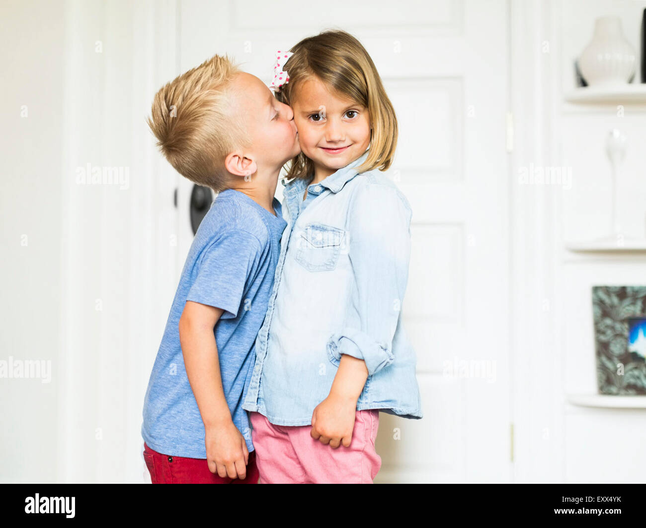 Petit garçon (4-5) s'embrasser sœur (4-5) Photo Stock