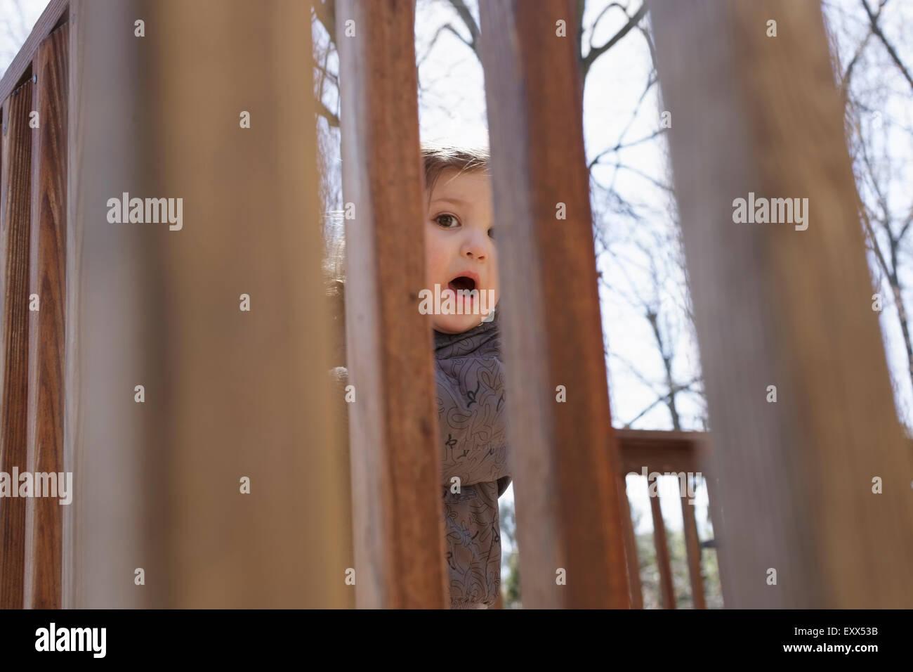 Portrait de jeune fille se cacher derrière une clôture Photo Stock
