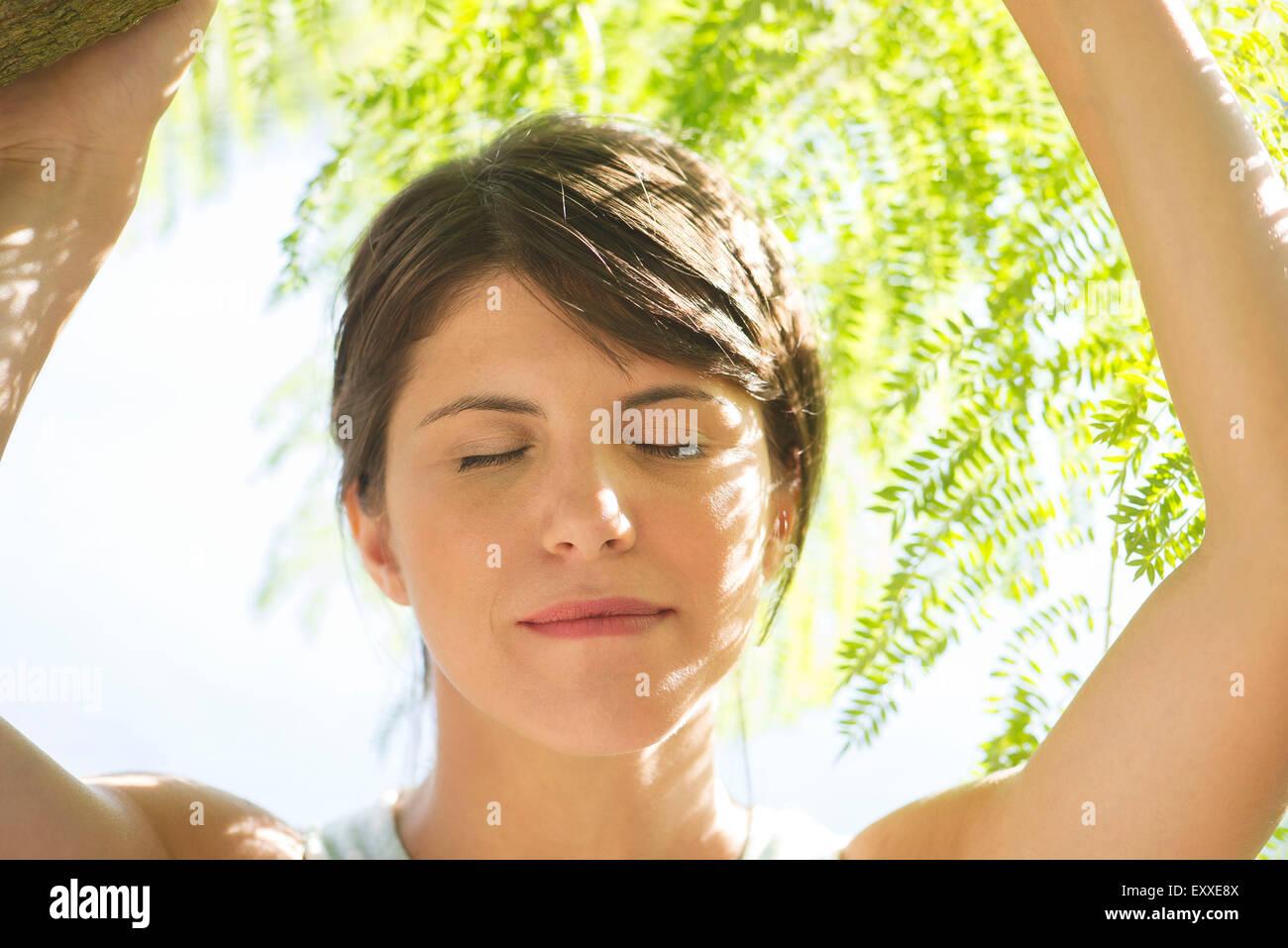 Femme à l'ombre des feuillages, les yeux clos, portrait Photo Stock