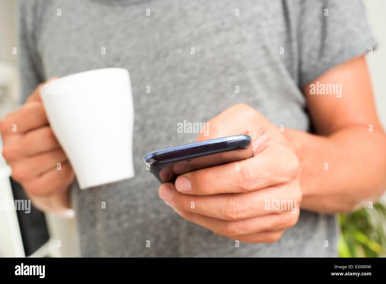 Libre d'un jeune homme de race blanche dans un tshirt gris à l'aide d'un smartphone à l'intérieur Photo Stock
