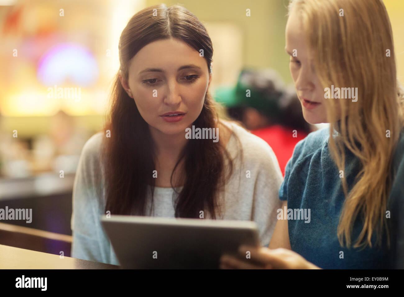 Deux femmes ont une discussion au restaurant à l'aide de tablette électronique Photo Stock