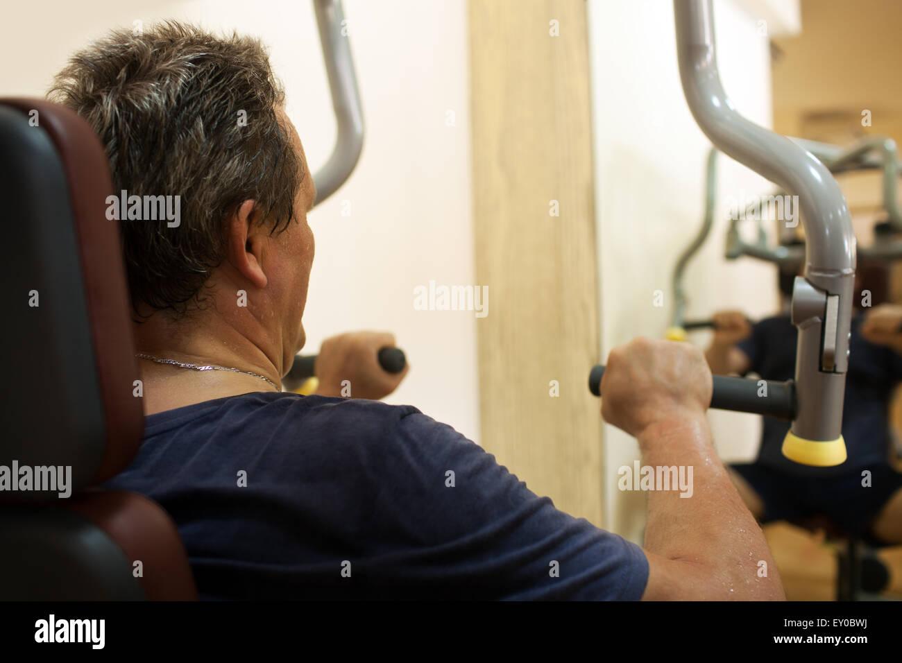 L'exercice de l'homme sur la machine de presse de l'épaule Photo Stock