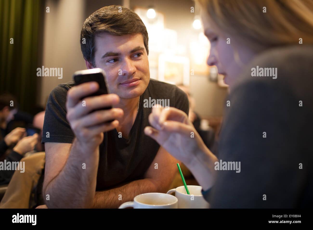 L'homme à l'aide de téléphone mobile pendant une réunion avec girl in cafe Photo Stock