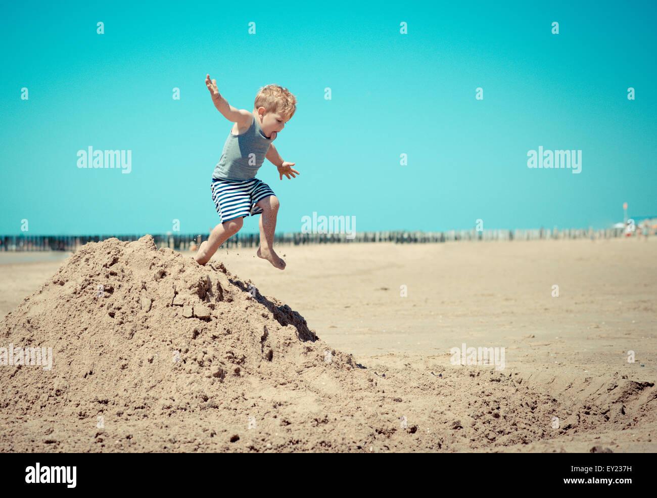 Petit garçon enfant sur la plage d'un saut d'une colline Photo Stock
