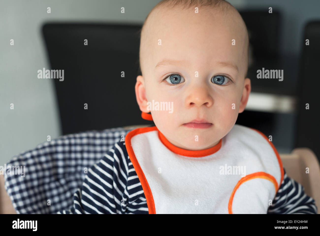 Portrait de bébé garçon regardant dans une chaise haute Photo Stock