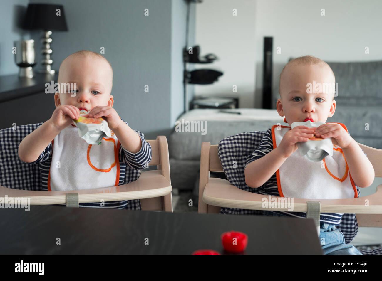 Les frères jumeaux bébé boire du jus dans des chaises hautes Banque D'Images