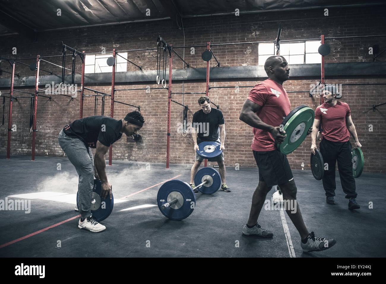 Les hommes déménagement barbells in gym Photo Stock
