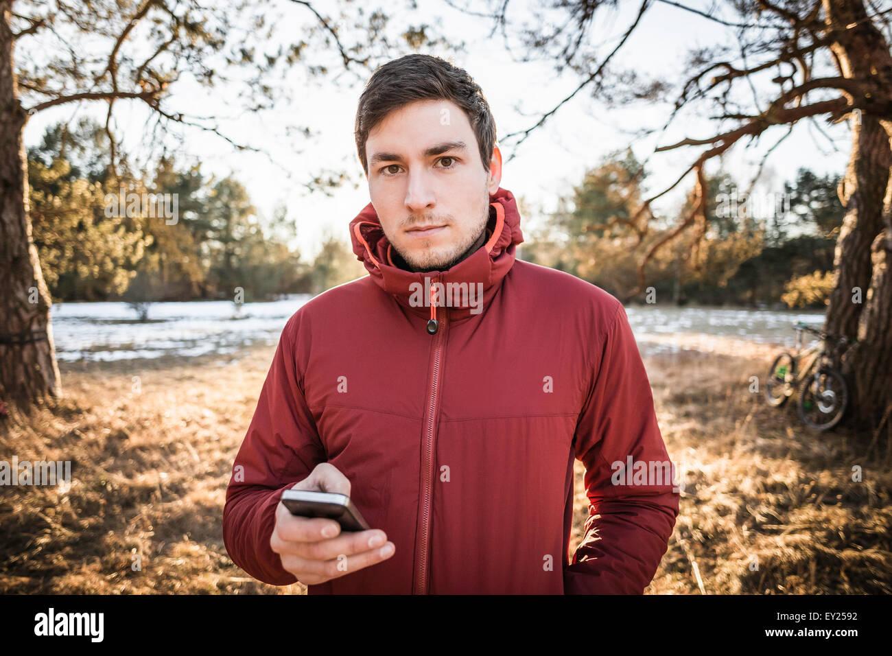 Jeune male hiker using smartphone en forêt au bord du lac Photo Stock