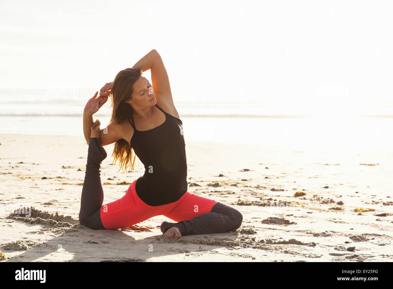 Woman in yoga pose sur plage Photo Stock