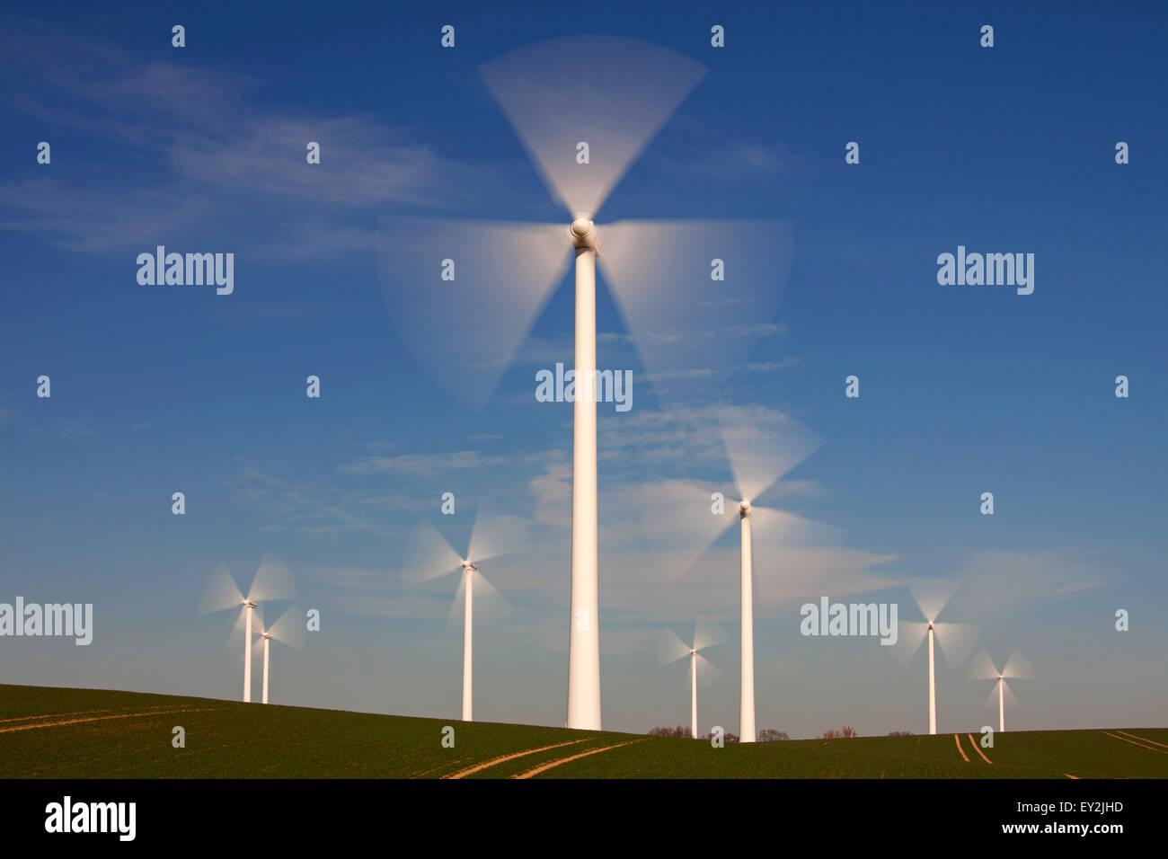 Les lames en rotation des éoliennes au parc contre le ciel bleu Photo Stock