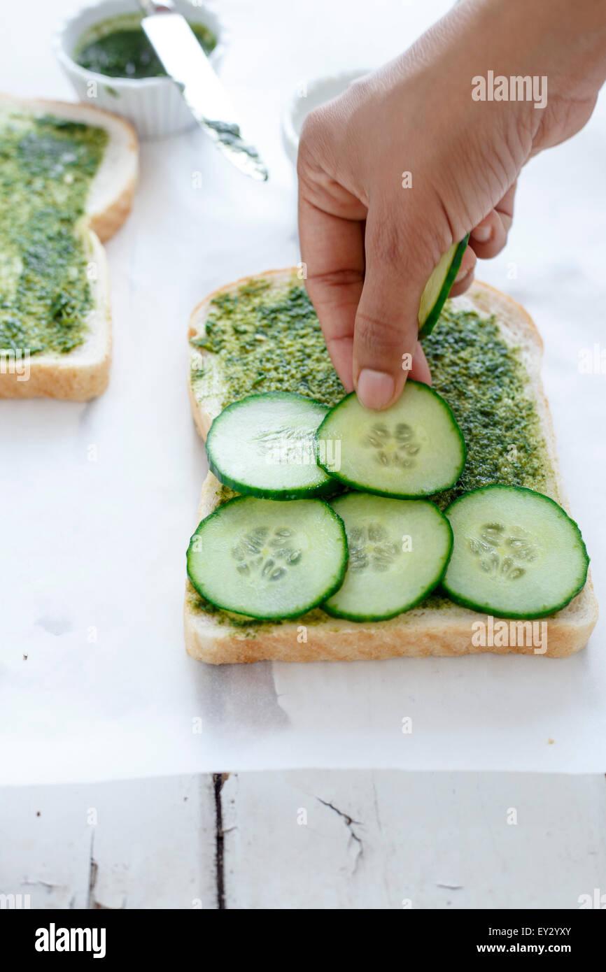 Placer les tranches de concombre chutney de coriandre propagation sur le pain. Photo Stock
