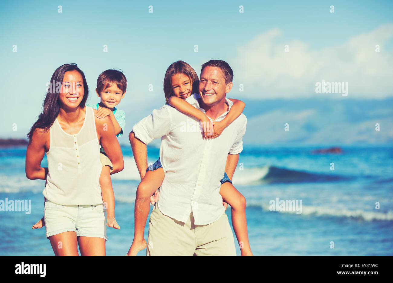 Young Happy Family having fun sur la plage en plein air Photo Stock