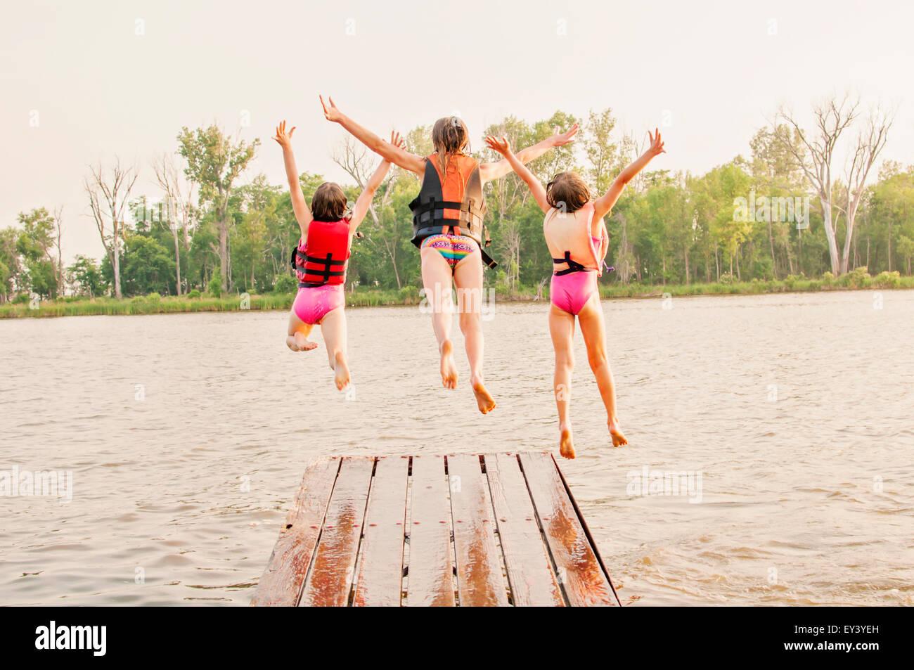 Trois filles jump off dock dans le lac Photo Stock
