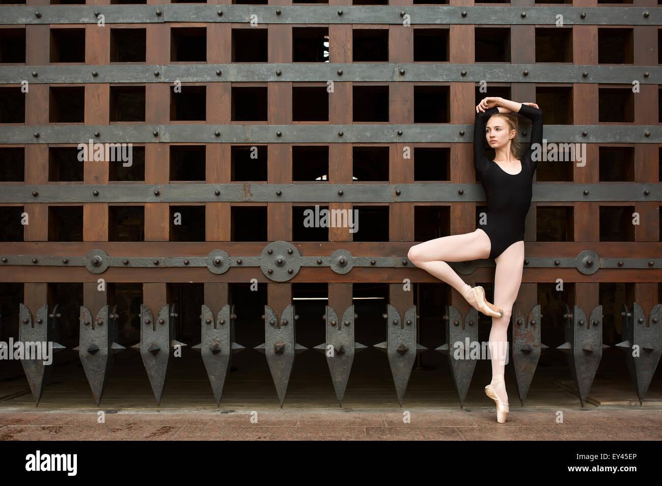 Danseuse Slim se tient sur une jambe près de l'ancienne porte Photo Stock