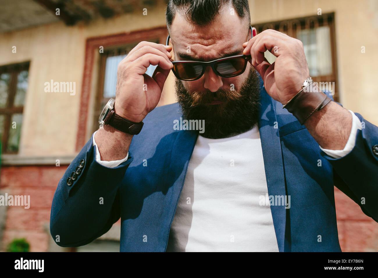 Homme barbu cool élégant enlève ses lunettes Photo Stock