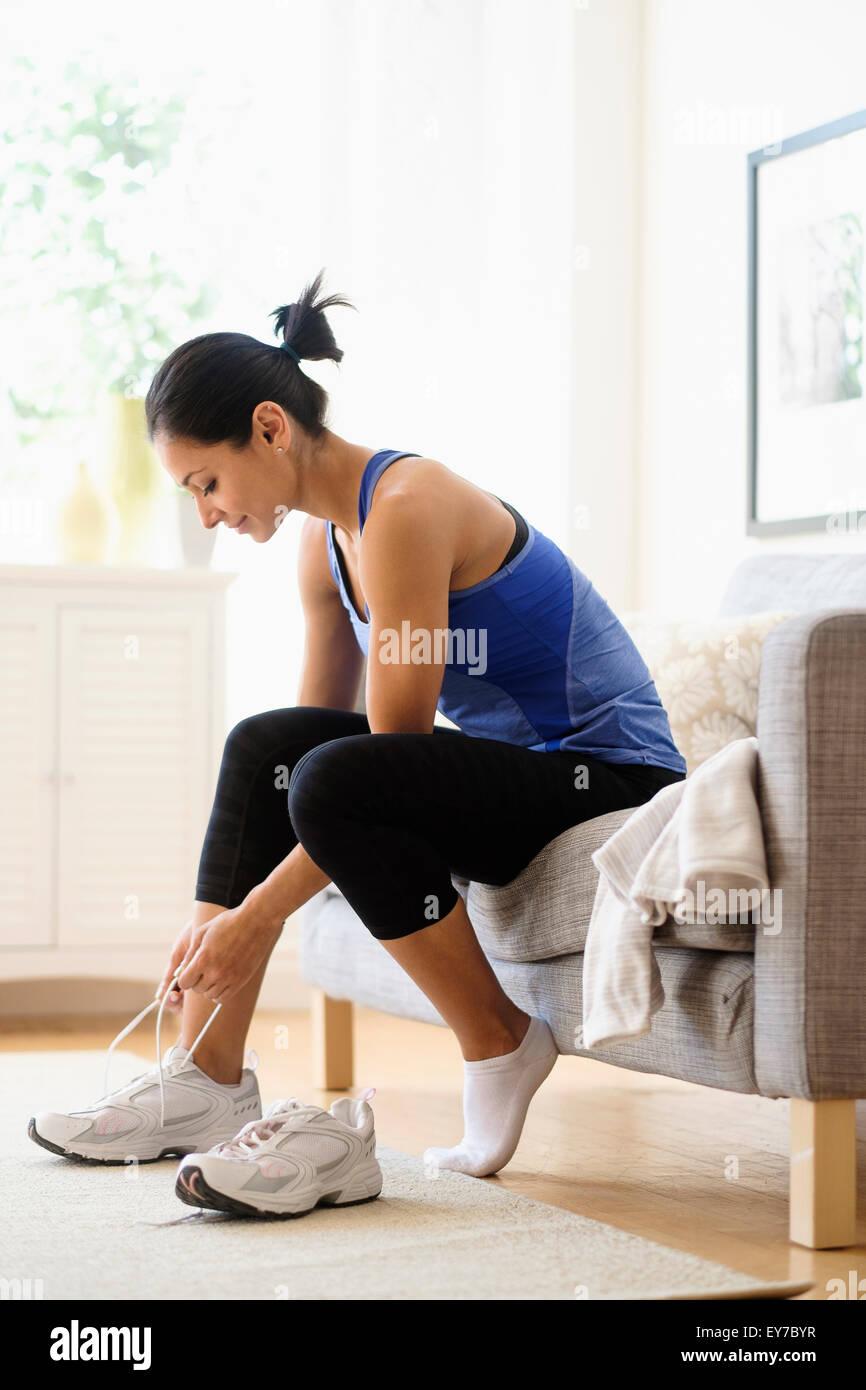Jeune femme mettre sur les chaussures Photo Stock