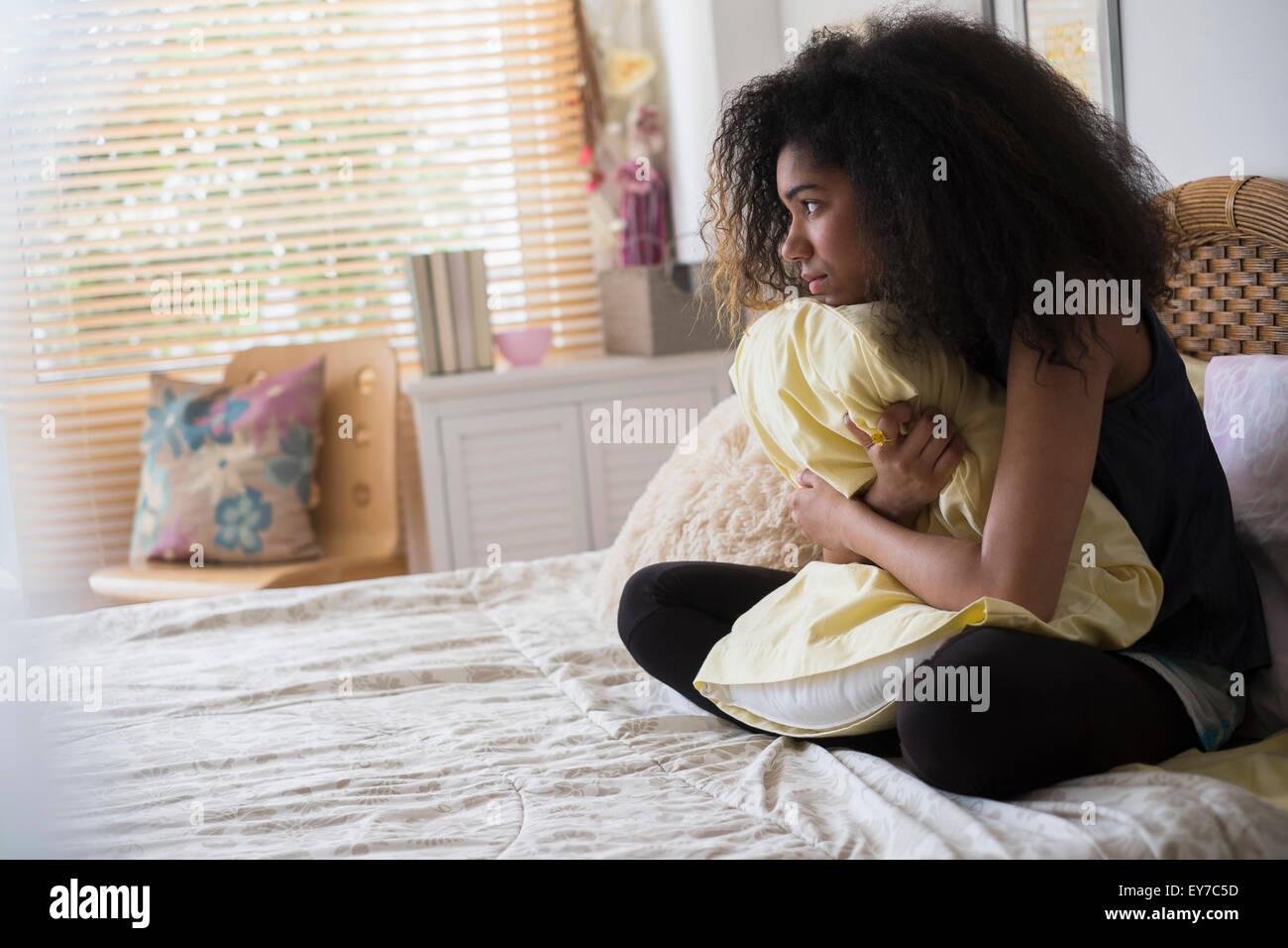 Teenage girl (14-15) assis sur le lit, embrassant oreiller Photo Stock