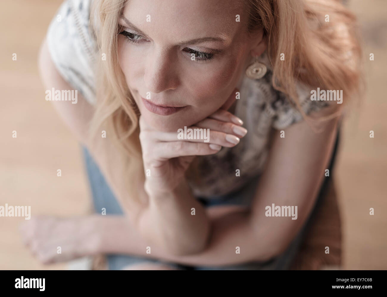 Mid-adult woman sitting on chair, la pensée Photo Stock