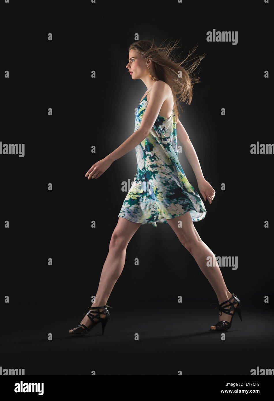 Studio shot of young woman walking Banque D'Images