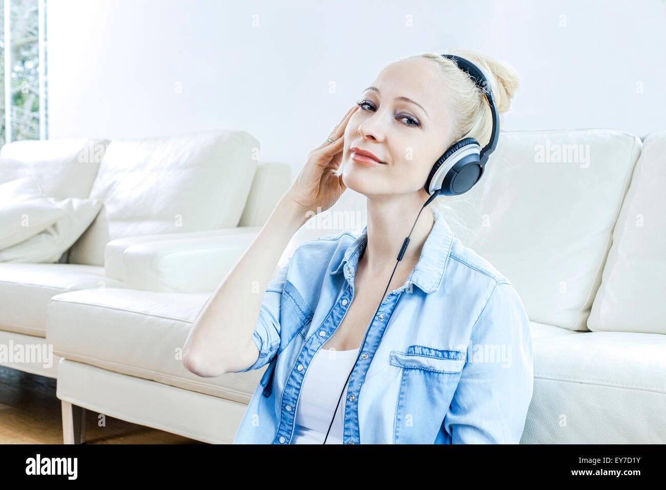 Femme blonde à écouter de la musique avec des écouteurs Photo Stock