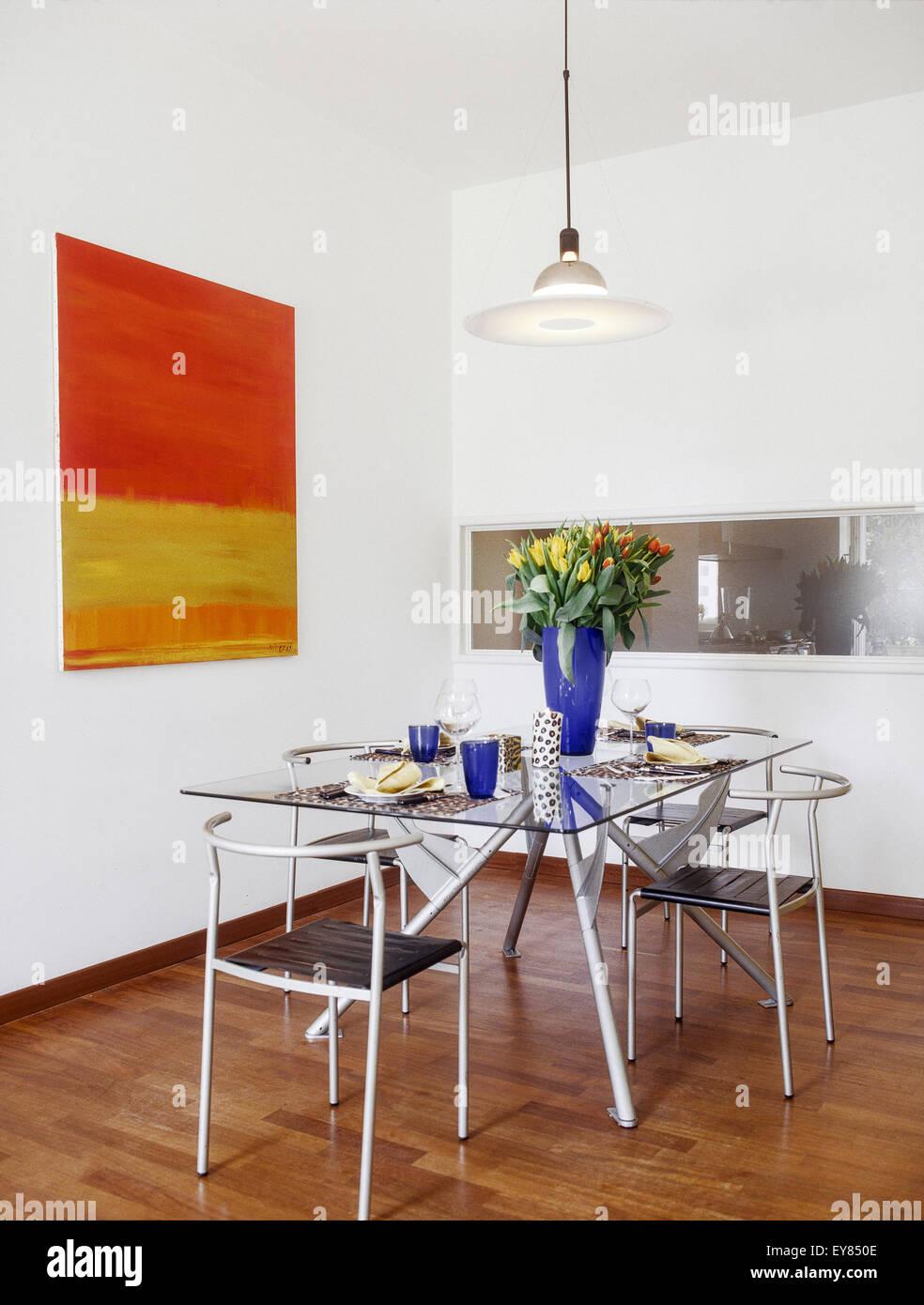 Avant-plan d'une table à manger avec des plats de verre et vase de tulipes sur elle Photo Stock