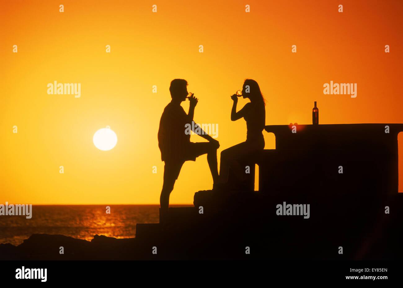 Couple buvant un verre de vin au coucher du soleil le long des côtes de l'Uruguay Photo Stock