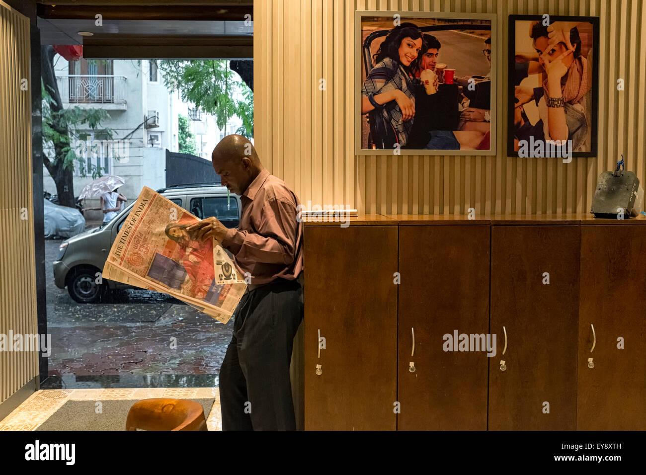 Un homme est vu lire un journal dans un café à Mumbai Photo Stock