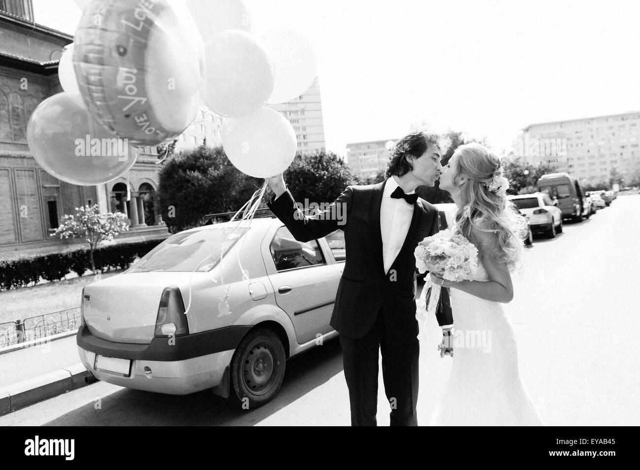 Les jeunes mariés couple kissing on a street. Image en noir et blanc avec film grain ajouté comme effet. Photo Stock