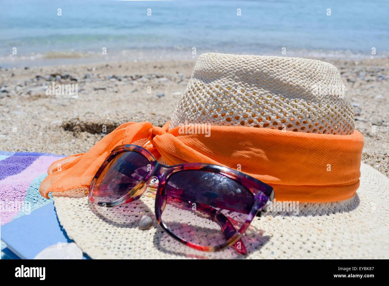 lunettes de soleil chapeau de paille et un livre sur la plage avec vue sur la mer dans le fond. Black Bedroom Furniture Sets. Home Design Ideas