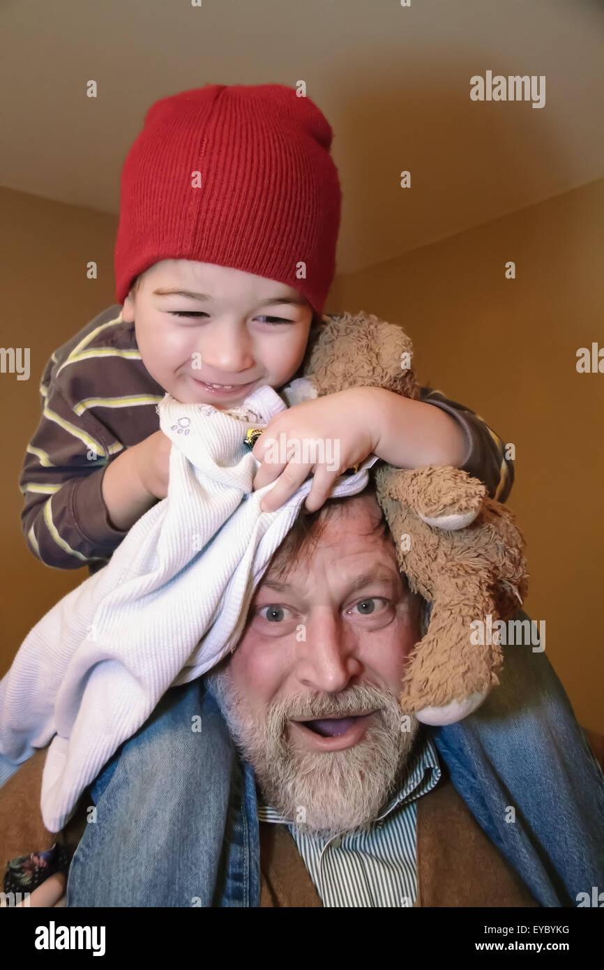 Trois ans à cheval sur les épaules de son grand-père, serrant son ours en peluche et une couverture, à Issaquah, Washington, USA Banque D'Images