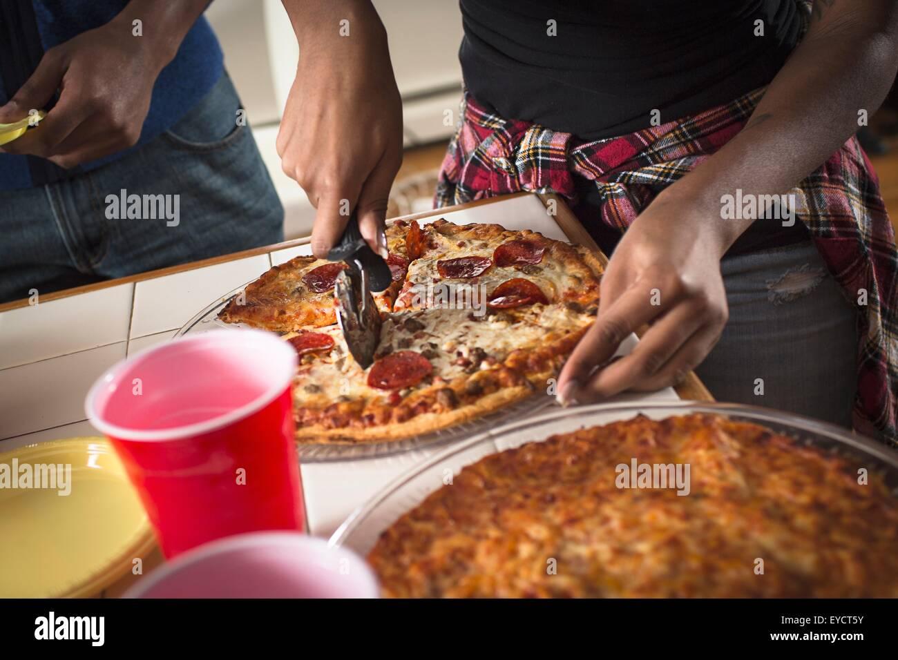 Portrait close up of womans mains cuisine pizza à découper Banque D'Images