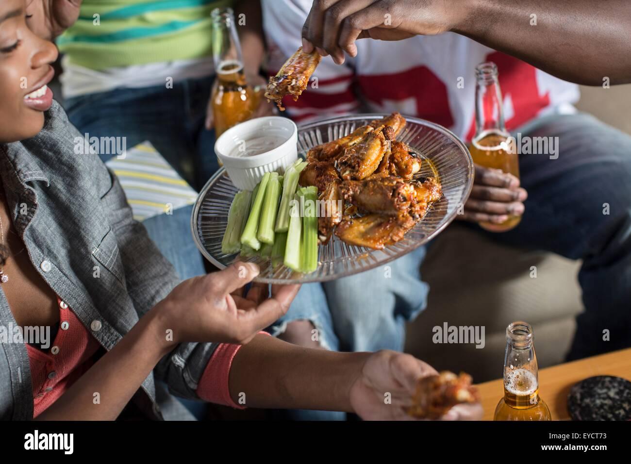 Groupe d'amis adultes partager sur des plats à emporter Salon canapé Photo Stock
