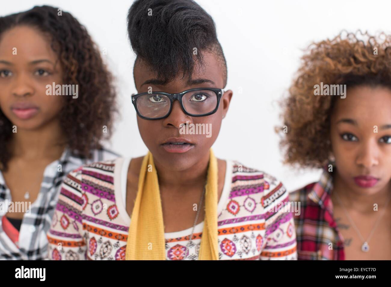 Portrait de trois jeunes femmes regardant grave les amis Photo Stock