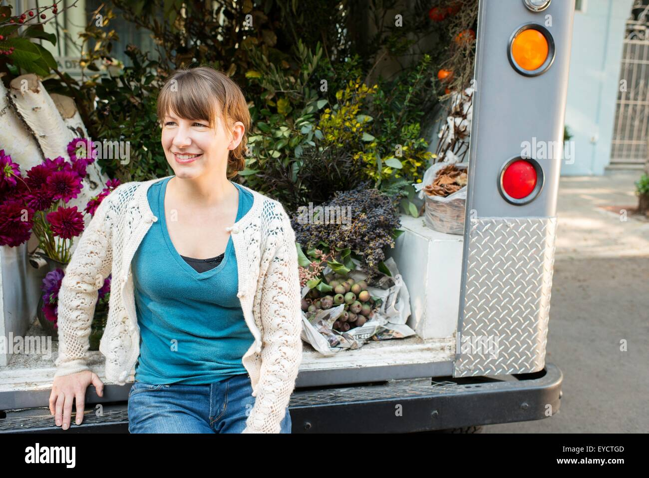 Portrait d'un fleuriste assis sur l'arrière du camion de livraison Banque D'Images
