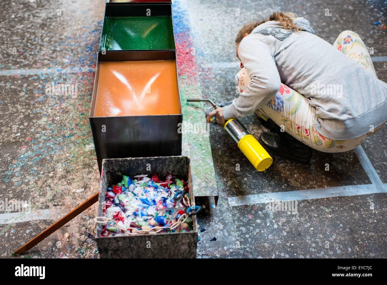 Femme accroupie pour faire fondre la cire née de l'association avec un chalumeau Banque D'Images