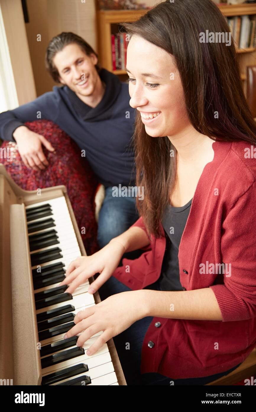 Jeune femme jouant du piano pour petit ami Photo Stock